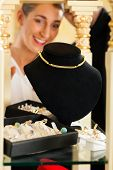 stock photo of collier  - Woman at the jeweller is looking for jewellery - JPG