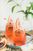 Italian Aperol Spritz Alcohol Cocktail With Ice And Blood Orange Slices On Table, Vertical Compositi poster