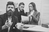 Business Quarrel. Man With Beard On Hopeful Face Holds Mug, Bosses, Coworkers, Colleagues On Backgro poster