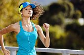 Portrait of a woman athlete runner training outdoors with cap and headphones listening to music. end