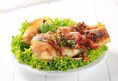 Gegrillte Fischfilets mit Kräutern auf Salat auf einem weißen Teller dekoriert