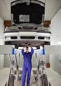 Mechanic standing while repairing a car in a garage