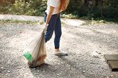 Girl Collects Garbage In Garbage Bags In Park poster