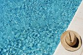 Straw Hat On The Side Of A Swimming Pool