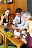 Happy business people having a meeting with laptop in a caf�?�©