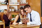 Business couple looking together at tablet computer in a caf�?�©
