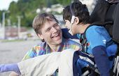 picture of biracial  - Father and disabled five year old son laughing together on beach - JPG