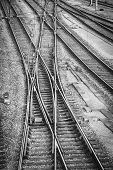 picture of railroad yard  - Railroad tracks and switches in a switching yard in black and white showing three parallel tracks with a set of tracks crossing all of them and the switches to control traffic - JPG