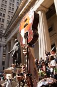 NEW YORK-JULY 11: An Occupy Guitarmy protester holds up his guitar in front of Federal Hall during the #99MileMarch from Philly to NYC on July 11, 2012 in New York, NY.
