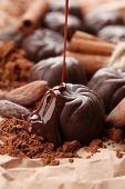 Composition of chocolate sweets, cocoa and spices on brown background