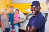 pic of trustworthiness  - trustworthy african auto mechanic standing in front of family inside garage - JPG