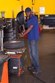 african tyre shop worker inflating a tyre with professional machine