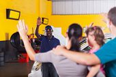 picture of bye  - friendly african auto repair shop worker waving good bye to customer - JPG
