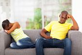 young african couple having conflict sitting on the sofa