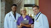 picture of medical office  - Three medical professionals stand together and smile.
