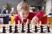 Young child making a move with a horse during a chess tournament at a school, with several other com