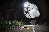 foto of murders  - Forensics researcher photographing a blood stained knife at a murder scene - JPG