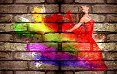 Graffiti of a woman in colorful dress on a brick wall