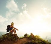 stock photo of wild adventure  - Hiker with backpack relaxing on a rock and enjoying sunset - JPG