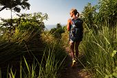 Hiker with backpack walking through a tropical lush meadow