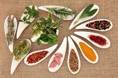 Spice and herb leaf selection in porcelain dishes and mortar with pestle over hessian background.