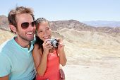 Tourists couple fun in Death Valley. Tourist woman and man taking pictures with camera enjoying the view and desert landscape of Zabriskie Point in Death Valley National Park, California, USA.