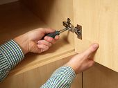 Closeup of carpenter's hands fitting wardrobe hinge doors in walk-in closet
