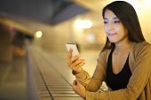 picture of japanese woman  - woman using smartphone in city at night - JPG