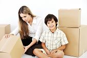 Beautiful woman and little smiling child openig cardboard box