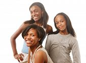 Three happy African American teenage girls on white background. Selective DOF, focus on the girl in front.