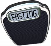 The word Fasting on a digital display of a scale to represent the new 5:2 diet fad or craze in which