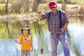 stock photo of grandpa  - Little Boy and His Grandpa catching a fish - JPG