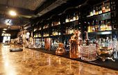 stock photo of copper  - Classic bar counter with bottles in blurred background - JPG