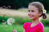 Summer joy - lovely girl blowing dandelion, happy child concept. Allergy season.