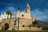 Statue of a woman against church of Sant Bartomeu i Santa Tecla in Sitges