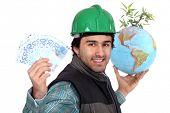 Laborer holding a globe, a green plant and twenty Euros bills