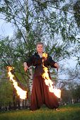 A girl in a black dress shows a fire show on nature in the evening.