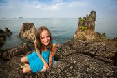 Teengirl in a blue dress in the rocks of the coast in Thailand.