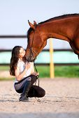 foto of bay horse  - Child riding a horse in meadow in spring - JPG