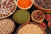 Different kinds of beans in bowls on  table close-up