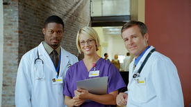 picture of medical office  - Three medical professionals stand together and smile. ** Note: Slight blurriness, best at smaller sizes - JPG