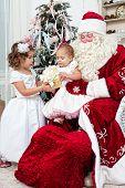 Saint Nicolas gives to small children Christmas gifts