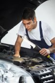 stock photo of car repair shop  - mechanic looking to car engine and holding lamp - JPG