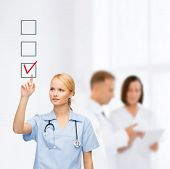 healthcare, medicine and technology concept - smiling young doctor or nurse pointing to red checkmar