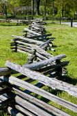 image of split rail fence  - A split rail fence disappearing into the distance by a green field  - JPG