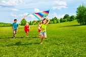 stock photo of kites  - Four little kids running in the park with kite happy and smiling - JPG