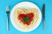 Cooked spaghetti carefully arranged in  heart shape and topped with tomato sauce, on color backgroun