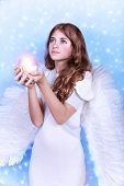 Cute Christmas angel on blue snowy background, adorable girl with candle in hands, religious winter