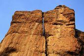 stock photo of karnataka  - Huge rock surfaces soaked in morning sunlight with rich blue sky at Badami Karnataka India Asia - JPG