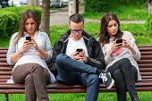 picture of beside  - Group of friends two women and one man, sitting on a bench in park separately looking at their phones loosing communication. people using their phones and sending texts as they stand beside each other